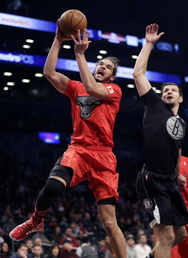 Chicago Bulls' Joakim Noah, left, drives to the basket past Brooklyn Nets' Mirza Teletovic during the first half of the NBA basketball game at the Barclays Center Wednesday, Dec. 25, 2013, in New York. (AP Photo/Seth Wenig)