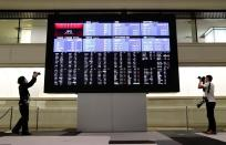 Photographers take photos near a large screen showing stock prices at the Tokyo Stock Exchange after market opens in Tokyo