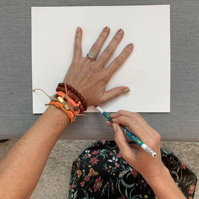 <p>Grab a fresh sheet of white computer paper and trace the outline of your hand using a sharp pencil. Tip: You might want to remove bracelets and bling for smoother lines ... unlike me!</p>