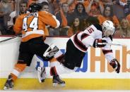 New Jersey Devils' Petr Sykora (15), of the Czech Republic, goes flying after a check from Philadelphia Flyers' Kimmo Timonen (44), of Finland, during the second period of Game 5 of a second-round NHL hockey Stanley Cup playoff series, Tuesday, May 8, 2012, in Philadelphia. (AP Photo/Matt Slocum)