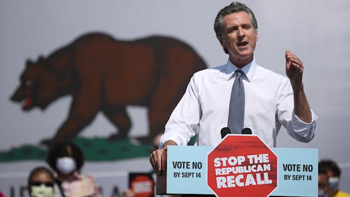 California Gov. Gavin Newsom stands at a podium with a sign reading: Vote no by Sept. 14, Stop the Republican recall.