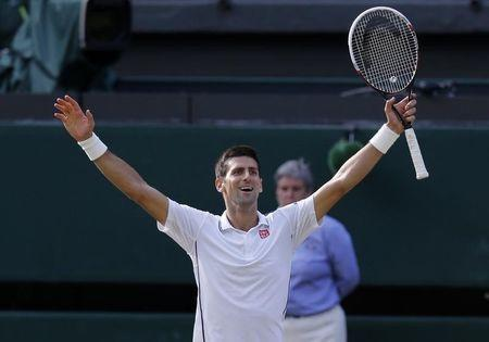 Novak Djokovic of Serbia celebrates defeating Roger Federer of Switzerland in their men's singles final tennis match at the Wimbledon Tennis Championships, in London July 6, 2014. REUTERS/Suzanne Plunkett