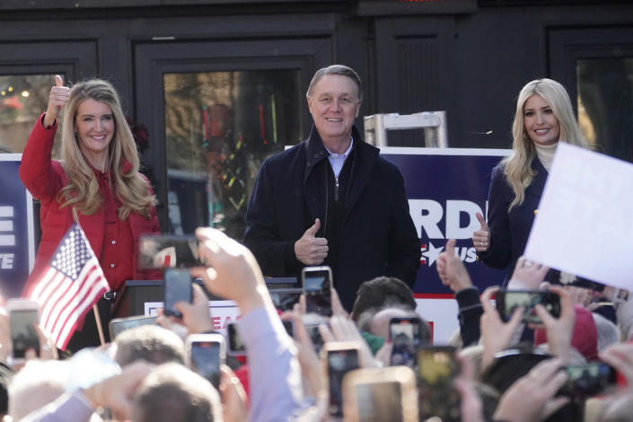 Sen. Kelly Loeffler, R-Ga., left, stands with Sen. David Perdue, R-Ga., and Ivanka Trump, Assistant to the President, during a campaign rally, Monday, Dec. 21, 2020, in Milton, Ga. (AP Photo/John Bazemore)