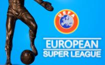 "A metal figure of a football player with a ball is seen in front of the words ""European Super League"" and the UEFA logo in this illustration"