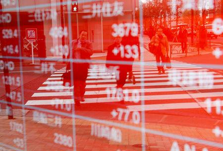 FILE PHOTO: Pedestrians are reflected on an electronic board showing stock prices outside a brokerage in Tokyo, Japan December 27, 2018. REUTERS/Kim Kyung-Hoon