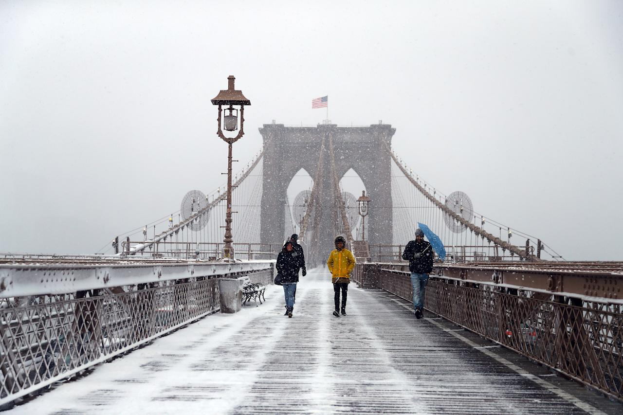 <p>Pedestrians cross the Brooklyn Bridge in New York City as a spring storm hit the Northeast with strong winds and a foot or more of snow expected in some parts of the region on Wednesday, March 21, 2018. (Photo: Gordon Donovan/Yahoo News) </p>
