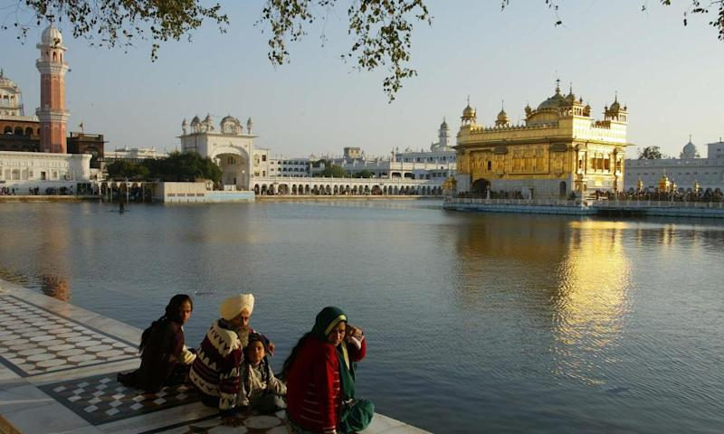 Pilgrims at the edge of the moat surrounding the Golden Temple in Amritsar, India.