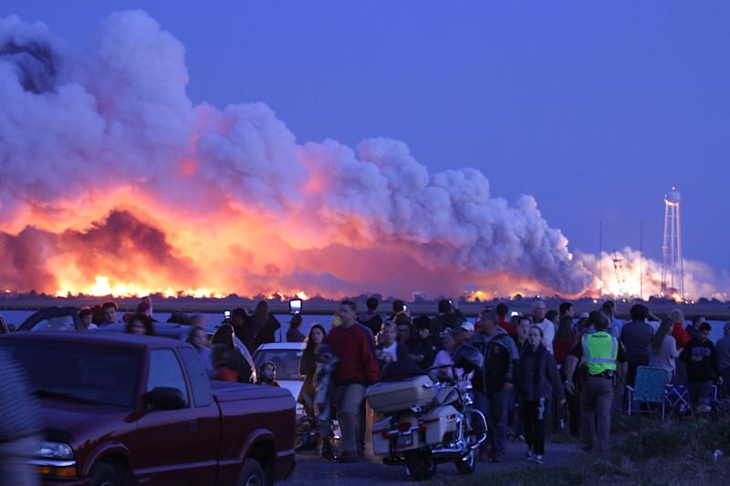 People who came to watch the launch of an unmanned rocket owned by Orbital Sciences Corporation look on after it exploded shortly after being launched on October 28, 2014 on Wallops Island, Virginia (AFP Photo/Steve Alexander)