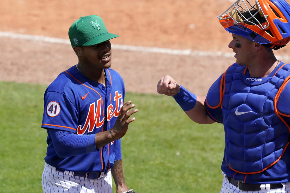 New York Mets starting pitcher Marcus Stroman, left, talks with catcher James McCann during the fifth inning of a spring training baseball game against the Washington Nationals, Thursday, March 18, 2021, in Port St. Lucie, Fla. (AP Photo/Lynne Sladky)