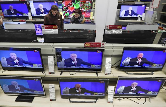 "Belarus's President Alexander Lukashenko is seen on TV screens inside a shop, broadcast during a briefing in Minsk, Belarus, Friday, Feb. 3, 2017. In the televised broadcast on Friday, Lukashenko asked the country's interior minister to press charges against Russia's top food safety official, alleging charges of ""damaging the state"" because Russia stopped the import of Belarusian products due to quality issues and suspicions that Belarus resells EU-made dairy products that are banned in Russia. The Kremlin responded to the outburst, listing the loans and reduced taxes Russia gave to Belarus. (AP Photo/Sergei Grits)"