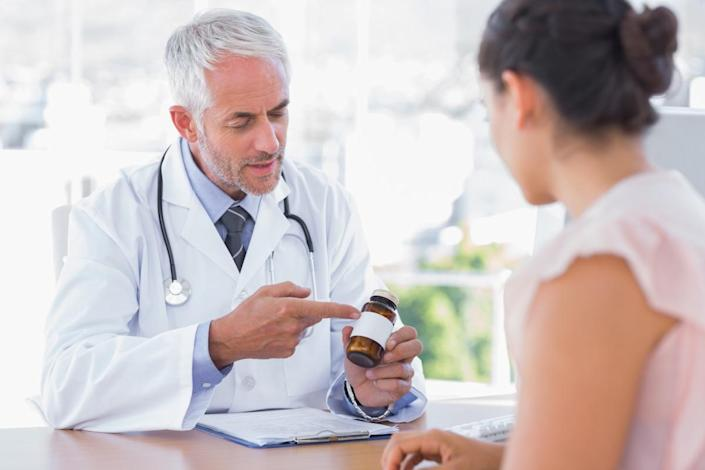 Doctor explaining the bottle of pills to patient in the office at desk