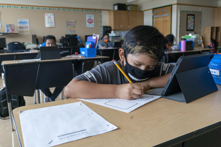 FILE - A student wears a face mask while doing work at his desk at the Post Road Elementary School, in White Plains, N.Y., in this Thursday, Oct. 1, 2020, file photo. U.S. health officials say the highly contagious delta version of the coronavirus is behind changes to mask guidelines. The Centers for Disease Control and Prevention this week announced that fully vaccinated people should resume wearing masks indoors if they live in areas where the virus is surging. CDC officials said new information about the spread of the delta variant forced them to reverse course. The agency also said teachers and students everywhere should go back to wearing masks in schools. (AP Photo/Mary Altaffer, FIle)