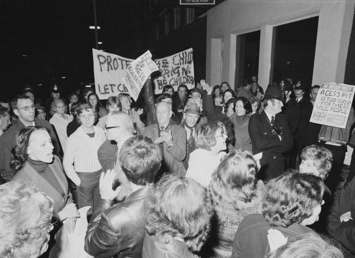 Protestors and police outside Conway Hall as the pro-paedophile activist group, the Paedophile Information Exchange (PIE) holds its first open meeting, London, 19th September 1977. Members of PIE were attacked and pelted with eggs, stink bombs and rotten fruit as they arrived at the meeting. Some of the protestors (centre and right) are carrying placards produced by the far-right National Front party, one of which reads: 'A cess pit is too good for these vile people'. (Photo by Malcolm Clarke/Keystone/Hulton Archive/Getty Images)