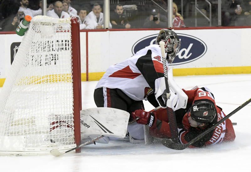 New Jersey Devils center Jack Hughes, right, slides into Ottawa Senators goaltender Craig Anderson during the second period of an NHL hockey game Wednesday, Nov. 13, 2019, in Newark, N.J. (AP Photo/Bill Kostroun)
