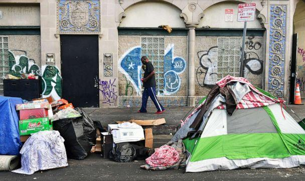 PHOTO: A man walks past tents housing the homeless on the streets  in the Skid Row community of Los Angeles, April 26, 2021. (Frederic J. Brown/AFP via Getty Images, FILE)