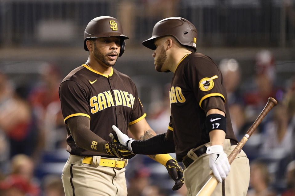 San Diego Padres' Tommy Pham, left, is greeted by Victor Caratini, right, after scoring on a double by Eric Hosmer during the fourth inning of a baseball game against the Washington Nationals, Friday, July 16, 2021, in Washington. (AP Photo/Nick Wass)