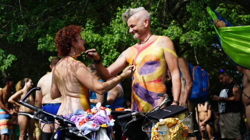 In this photo provided by David Cimetta, Melanie and Jim OâConnor paint each other's nude body while standing next to their bicycles before the start of the Philly Naked Bike Ride in Philadelphia on Saturday Aug. 24, 2019. (David Cimetta via AP)