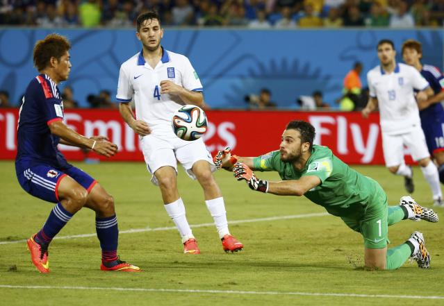 Greece's Orestis Karnezis (R) dives forward to intercept the ball in front of Japan's Yoshito Okubo (L) and teammate Kostas Manolas (C) during their 2014 World Cup Group C soccer match against Japan at the Dunas arena in Natal June 19, 2014. REUTERS/Kai Pfaffenbach (BRAZIL - Tags: SOCCER SPORT WORLD CUP)
