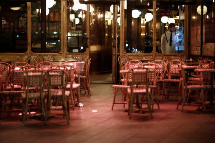 A waiter stands inside his empty restaurant and prepares the closure of the place, as France's Prime Minister announced to close most all non-indispensable locations from midnight on Saturday, in Paris
