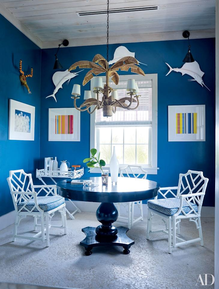 """Painted in a Benjamin Moore blue, the card room in designer Alessandra Branca's <a rel=""""nofollow"""" href=""""http://www.architecturaldigest.com/story/alessandra-branca-harbour-island-bahamas-vacation-home-article?mbid=synd_yahoo_rss"""">Bahamas vacation home</a> includes photographs by Tema Stauffer (left) and Jonathan Lewis and a table by Jayson Home."""