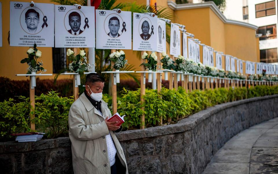 Images of the 125 doctors who have died during the pandemic in Peru, displayed outside Peru's Medical College (CMP) in Lima - AFP