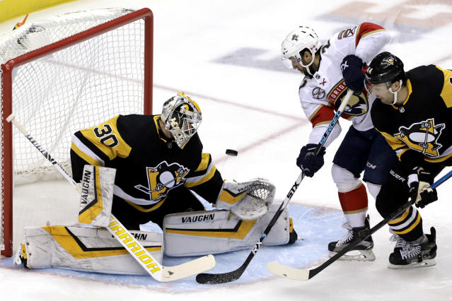Florida Panthers' Vincent Trocheck, center, looks for a rebound as a shot by Henrik Borgstrom gets past Pittsburgh Penguins goaltender Matt Murray (30) with Erik Gudbranson, right, defending during the first period of an NHL hockey game in Pittsburgh, Tuesday, March 5, 2019. (AP Photo/Gene J. Puskar)