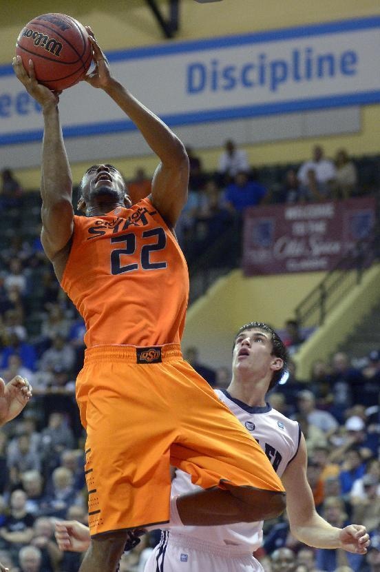 Oklahoma State forward Markel Brown (22) goes up for a shot in front of Butler guard Kellen Dunham during the first half of an NCAA college basketball game at the Old Spice Classic tournament in Kissimmee, Fla., Friday, Nov. 29, 2013.(AP Photo/Phelan M. Ebenhack)
