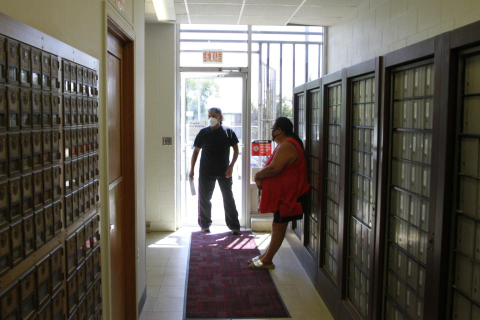 People wait to check their post office boxes in Mission, S.D. on Aug. 6, 2020. The post office is one of four on the Rosebud Indian Reservation. Voter advocates say that people living on reservations must make long trips to check their mail. (AP Photo/Stephen Groves)