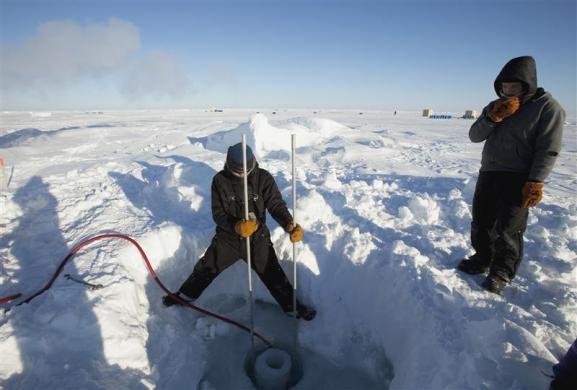 Applied Physics Laboratory Ice Station (APLIS) employee Keith Magness (L) and Nick Michel-Hart cut a hole in the Arctic ice to hang sonar instrumentation for research at the 2011 Arctic APLIS camp north of Prudhoe Bay, Alaska March 18, 2011.