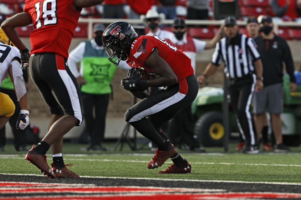 Texas Tech's Trey Cleveland (85) runs the ball to score a touchdown during the first half of an NCAA football game against West Virginia, Saturday, Oct. 24, 2020, in Lubbock, Texas. (AP Photo/Brad Tollefson)