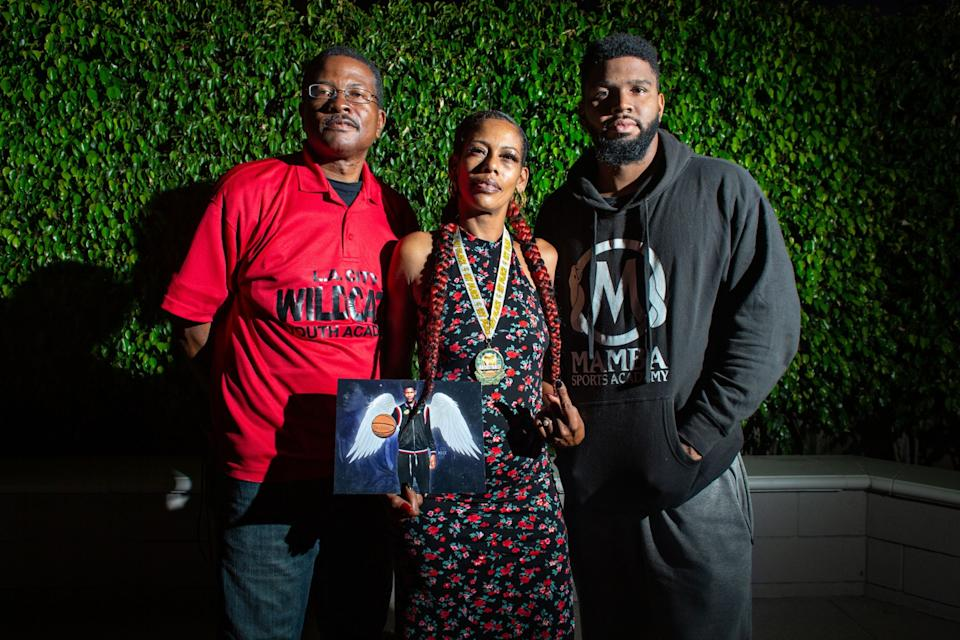 "Taloma Miller holds a photo of her late son Semaj. With her are L.A. City Wildcats director Derrick Cooper, left, and Wildcats Coach Keilan Thompson. <span class=""copyright"">(Jason Armond / Los Angeles Times)</span>"
