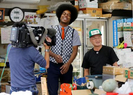 Japanese television personality Jun Soejima is filmed for public broadcast breakfast show with a greengrocer at the latter's shop in Tokyo, Japan, September 12, 2018. Picture taken September 12, 2018.  REUTERS/Toru Hanai