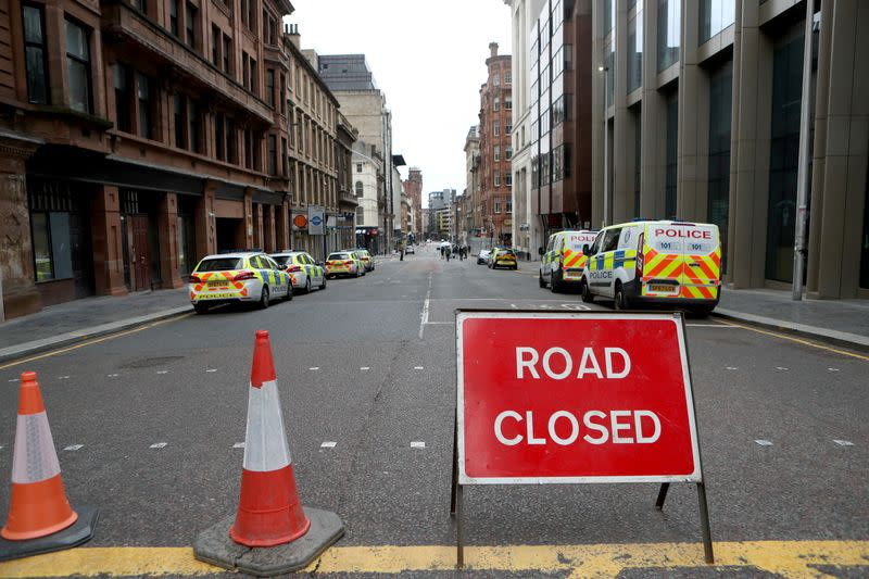 Police vehicles are seen parked near the scene of reported multiple stabbings at West George Street in Glasgow