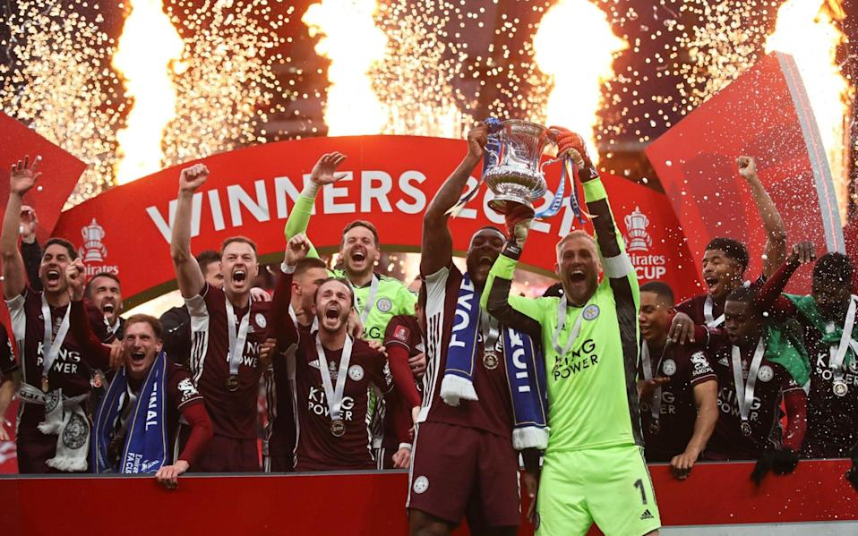 Leicester's goalkeeper Kasper Schmeichel, right, and Leicester's Wes Morgan lift the trophy after winning the FA Cup final soccer match between Chelsea and Leicester City - PA