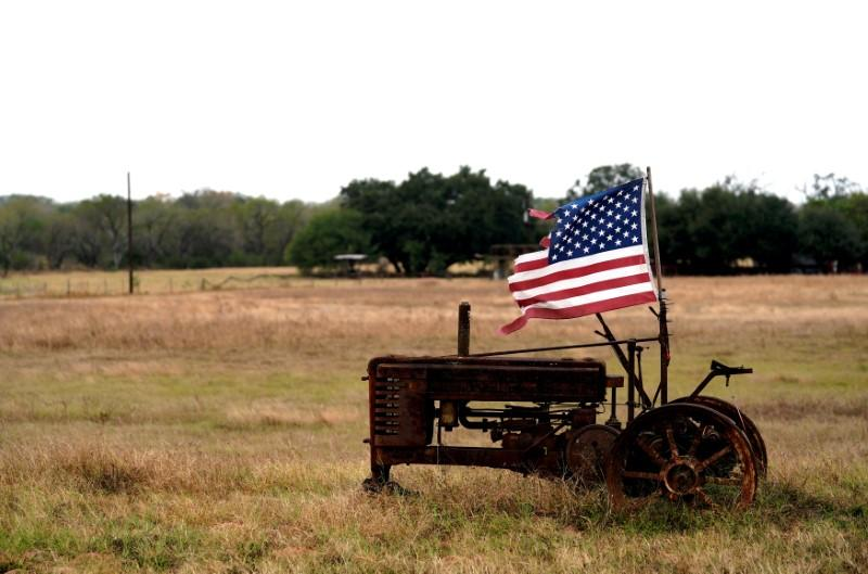 FILE PHOTO: A tattered U.S. flag flies on an old tractor in a farm field outside Sutherland Springs