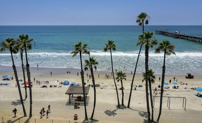 Beach-goers take to the water on a warm summer day at the San Clemente Pier