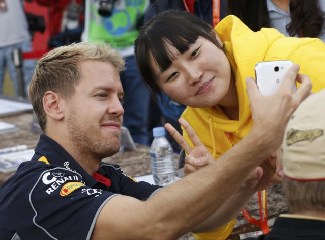 Red Bull Formula One driver Sebastian Vettel of Germany (L) takes a photograph with a fan after the qualifying session for the Korean F1 Grand Prix at the Korea International Circuit in Yeongam, October 5, 2013. REUTERS/Lee Jae-Won (SOUTH KOREA - Tags: SPORT MOTORSPORT F1)