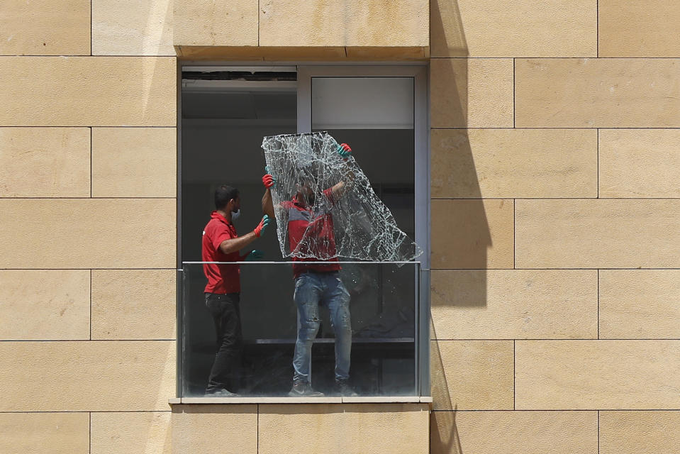 Workers throw a broken window from a damaged apartment a day after an explosion hit the seaport of Beirut, Lebanon, Wednesday, Aug. 5, 2020. Residents of Beirut confronted a scene of utter devastation on Wednesday, a day after a massive explosion at the port rippled across the Lebanese capital, killing at least 100 people, wounding thousands and leaving entire city blocks flooded with glass and rubble. (AP Photo/Hussein Malla)