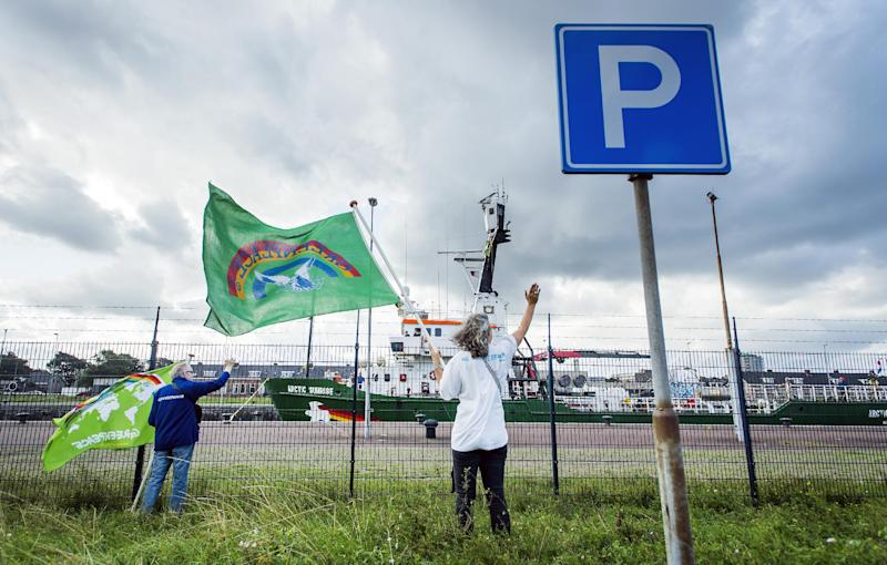 A woman holds a Greenpeace flag and waves as Greenpeace's Dutch-flagged Artic Sunrise ship returns to the Netherlands in IJmuiden harbour on August 9, 2014 (AFP Photo/Remko De Waal )