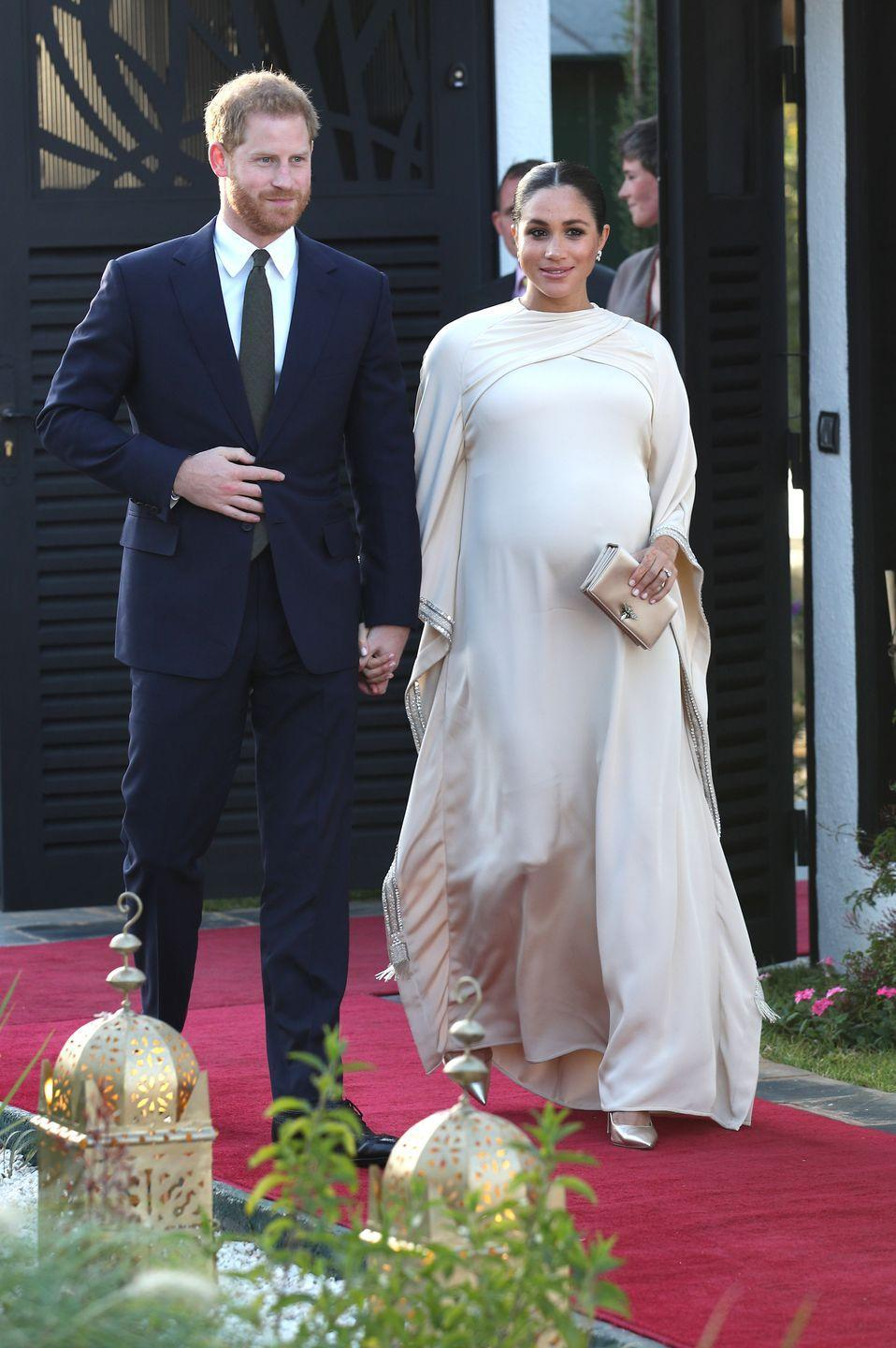 """<p>Meghan arrived at the British Ambassador residence wearing a gorgeous bespoke Dior gown. She paired the look with <a href=""""https://www.maisonbirks.com/en/birks-snowflake-snowstorm-diamond-earrings-in-white-gold"""" rel=""""nofollow noopener"""" target=""""_blank"""" data-ylk=""""slk:diamond earrings by Maison Birks"""" class=""""link rapid-noclick-resp"""">diamond earrings by Maison Birks</a>, which she <a href=""""https://www.townandcountrymag.com/style/fashion-trends/a24183870/meghan-markle-white-theia-gown-dinner-tonga-photo/"""" rel=""""nofollow noopener"""" target=""""_blank"""" data-ylk=""""slk:wore on her Oceanic tour"""" class=""""link rapid-noclick-resp"""">wore on her Oceanic tour</a>, <a href=""""https://go.redirectingat.com?id=74968X1596630&url=https%3A%2F%2Fus.vestiairecollective.com%2Fwomen-bags%2Fdior%2Fd-bee%2F&sref=https%3A%2F%2Fwww.townandcountrymag.com%2Fstyle%2Ffashion-trends%2Fg3272%2Fmeghan-markle-preppy-style%2F"""" rel=""""nofollow noopener"""" target=""""_blank"""" data-ylk=""""slk:a satin clutch"""" class=""""link rapid-noclick-resp"""">a satin clutch</a> and gold pumps, both by Dior. </p>"""