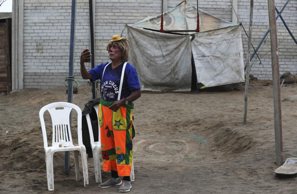"""Circus clown Santos Chiroque, whose performance name is """"Piojito,"""" or Little Tick, looks in a mirror as he shows off his costume outside his home on the outskirts of Lima, Peru, Monday, Aug. 10, 2020. Chiroque's family used to run their own small circus, but since March when the lockdown to curb COVID-19 closed their business, and the requirement for people over 60 to self-quarantine kept the 74-year-old at home, they started selling circus food like caramelized apples to survive. (AP Photo/Martin Mejia)"""