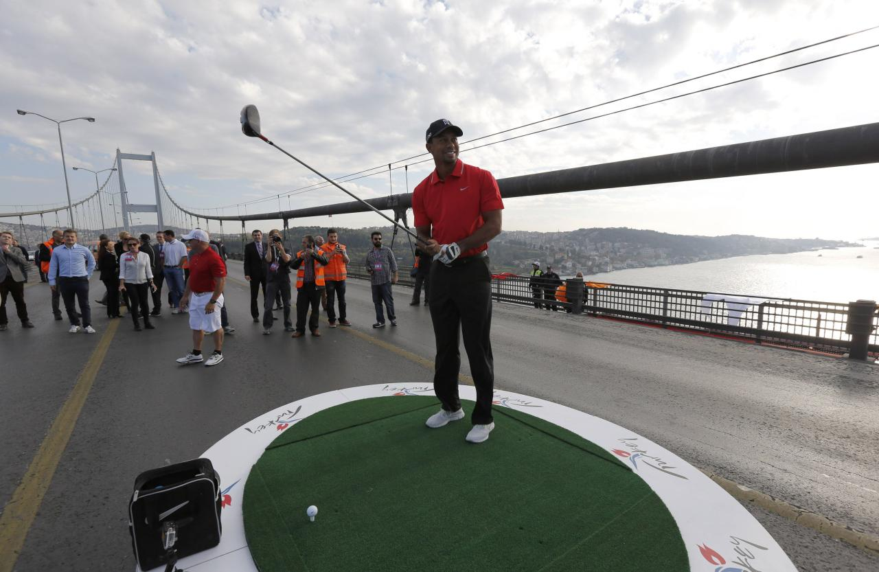U.S. golfer Tiger Woods gets ready to hit a shot during an event to promote the upcoming Turkish Airlines Open golf tournament, on the Bosphorus Bridge that links the city's European and Asian sides, in Istanbul November 5, 2013. Woods is in Turkey to attend the tournament, which will take place in Antalya, southern Turkey, between November 7 to 10. REUTERS/Murad Sezer (TURKEY - Tags: SPORT GOLF)