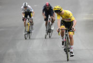 Slovenia's Tadej Pogacar, wearing the overall leader's yellow jersey, looks back to check if he has enough lead on Denmark's Jonas Vingegaard, wearing the best young rider's white jersey, and Richard Carapaz of Ecuador , as he crosses the finish line to win the eighteenth stage of the Tour de France cycling race over 129.7 kilometers (80.6 miles) with start in Pau and finish in Luz Ardiden, France,Thursday, July 15, 2021. (AP Photo/Christophe Ena)