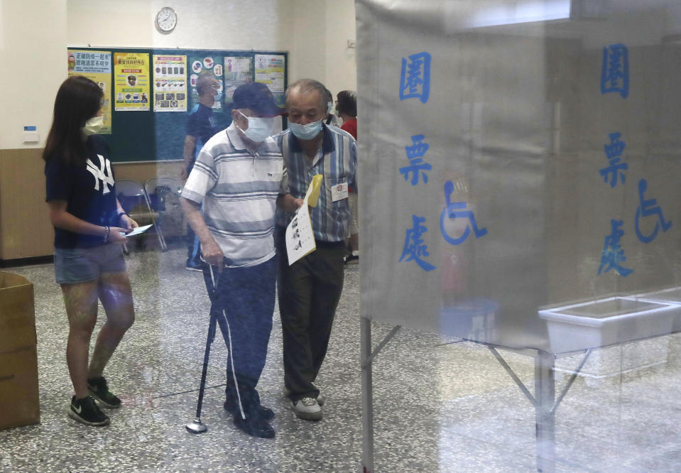 Members of the Nationalist Party, or KMT, prepare to cast their ballot for election of its party chairman at a polling station in Taipei, Taiwan, Saturday, Sept. 25, 2021. Fraught relations with neighboring China are dominating Saturday's election for the leader of Taiwan's main opposition Nationalist Party. (AP Photo/Chiang Ying-ying)