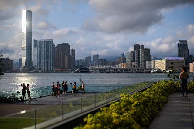 People gather to watch the sunset as they stand on a viewing platform in Tamar Park overlooking Victoria Harbour and the Kowloon skyline in Hong Kong on May 5, 2020. (PHOTO: ANTHONY WALLACE/AFP via Getty Images)