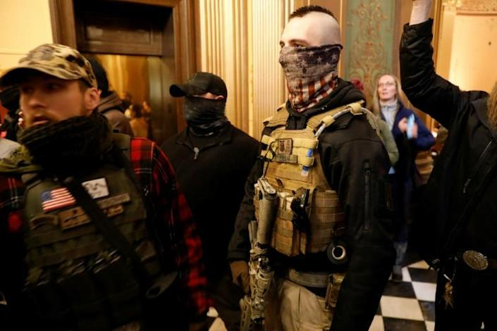 Armed protestors try to enter the Michigan state legislature to protest the coronavirus lockdown (AFP Photo/JEFF KOWALSKY)