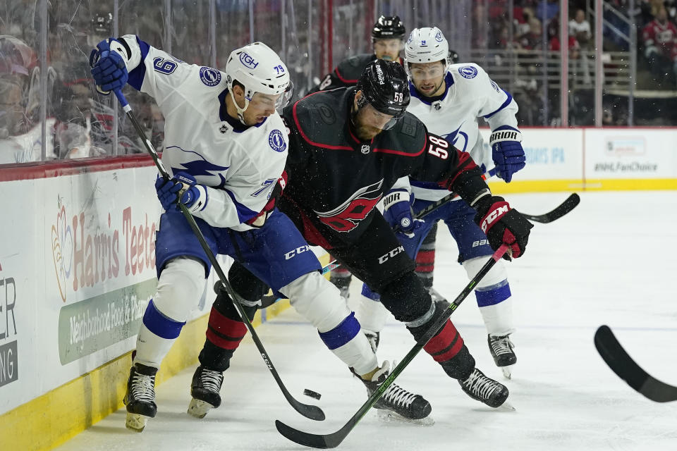 Carolina Hurricanes defenseman Jani Hakanpaa (58) struggles for the puck with Tampa Bay Lightning center Ross Colton (79) and center Tyler Johnson (9) during the second period in Game 1 of an NHL hockey Stanley Cup second-round playoff series in Raleigh, N.C., Sunday, May 30, 2021. (AP Photo/Gerry Broome)