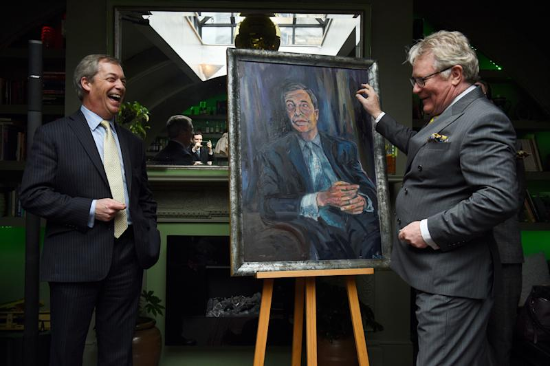 Nigel Farage stands beside a portrait of himself titled Mr Brexit by artist Dan Llywelyn Hall, with Comedian Jim Davidson (right), at L'Escargot Restaurant in London.