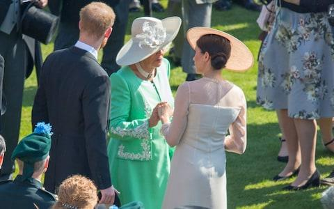 The Duchess of Cornwall clasps Meghan's hand a garden party at Buckingham Palace - Credit: ROTA