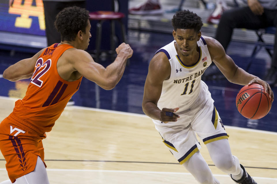 Notre Dame's Juwan Durham (11) drives in as Virginia Tech's Keve Aluma (22) defends during the first half of an NCAA college basketball game Wednesday, Jan. 27, 2021, in South Bend, Ind. (AP Photo/Robert Franklin)
